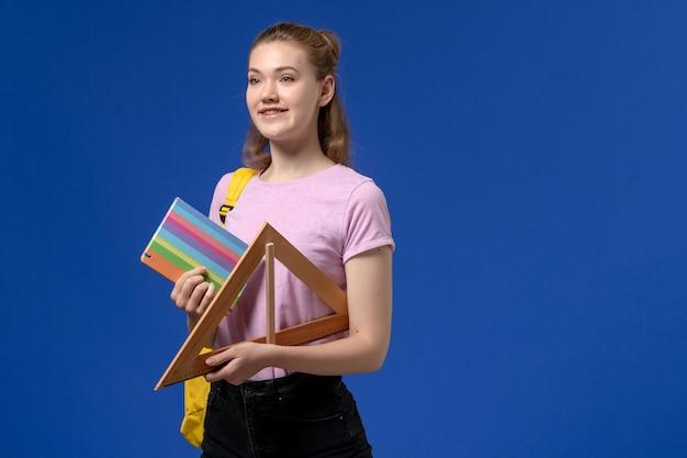 Vista frontal de uma jovem mulher com uma camiseta rosa segurando uma figura triangular de madeira e um caderno na parede azul