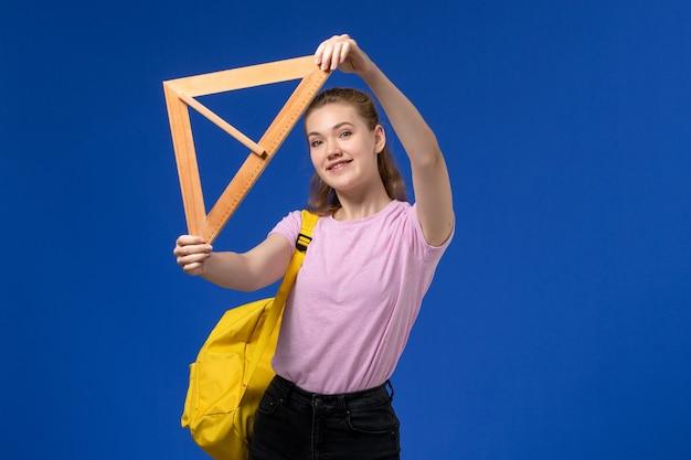 Vista frontal de uma jovem mulher com uma camiseta rosa segurando uma figura triangular de madeira sorrindo na parede azul