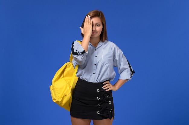 Vista frontal de uma jovem mulher de camisa azul com saia preta e mochila amarela, sorrindo na parede azul-clara