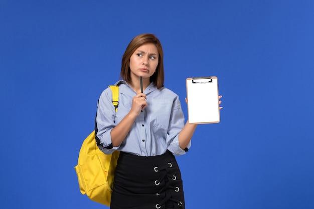 Vista frontal de uma jovem mulher de camisa azul com saia preta, mochila amarela e segurando uma caneta com o bloco de notas na parede azul