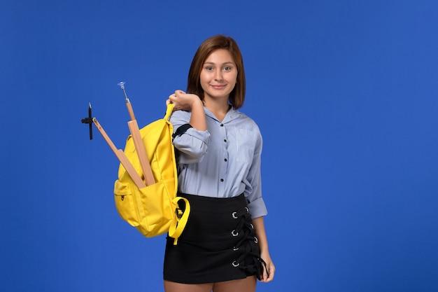 Vista frontal de uma jovem mulher de camisa azul com uma mochila amarela segurando uma figura de madeira sorrindo na parede azul-clara