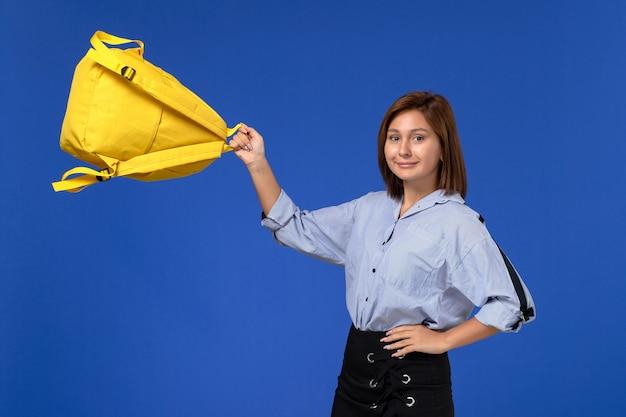 Vista frontal de uma jovem mulher de camisa azul e saia preta segurando sua mochila amarela com um sorriso na parede azul claro