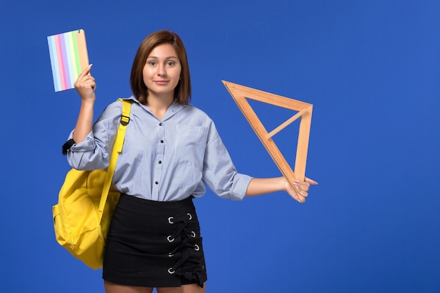 Vista frontal de uma jovem mulher de camisa azul segurando a forma de um triângulo de madeira e um caderno na parede azul