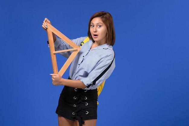 Vista frontal de uma jovem mulher de camisa azul segurando a forma de um triângulo de madeira na parede azul