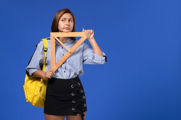 Vista frontal de uma jovem mulher de camisa azul, segurando um triângulo de madeira e pensando na parede azul