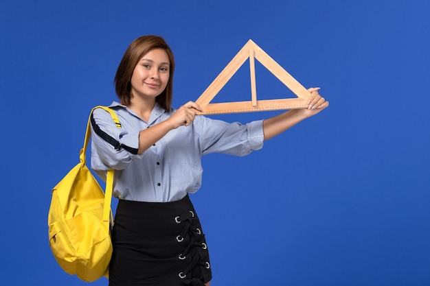 Vista frontal de uma jovem mulher de camisa azul segurando um triângulo de madeira e sorrindo na parede azul