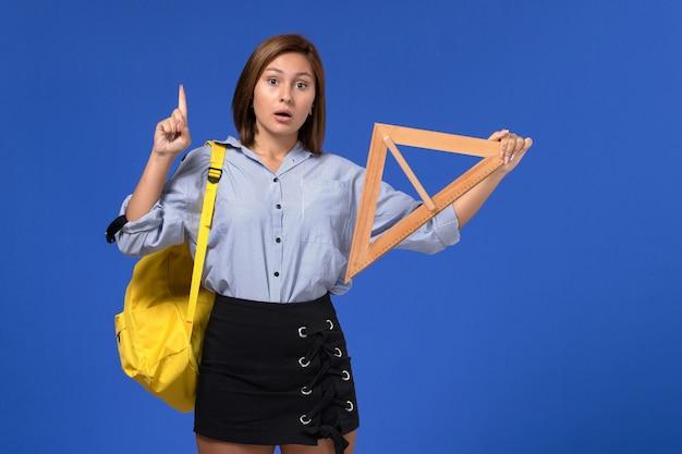 Vista frontal de uma jovem mulher de camisa azul segurando um triângulo de madeira na parede azul