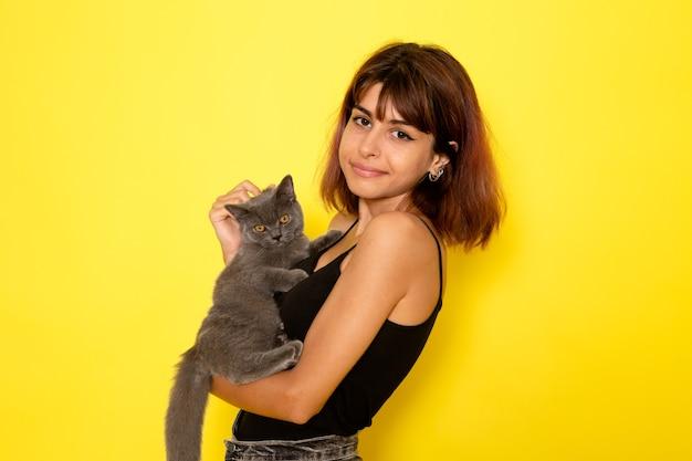 Vista frontal de uma jovem mulher de camisa preta e calça jeans cinza segurando um gatinho cinza na parede amarela