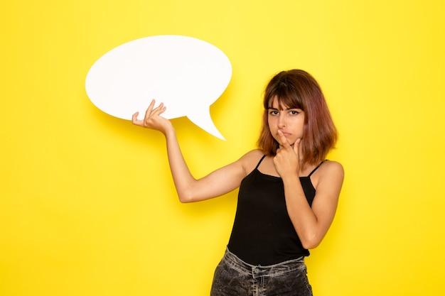 Vista frontal de uma jovem mulher de camisa preta e calça jeans cinza, segurando uma grande placa branca e pensando na parede amarela
