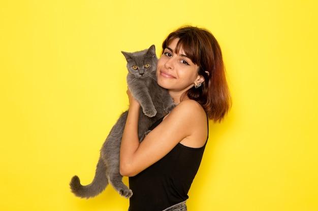 Vista frontal de uma jovem mulher de camisa preta sorrindo, segurando o gatinho na parede amarela