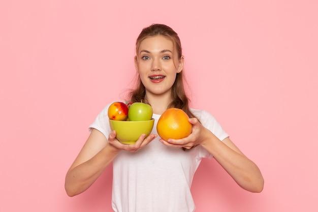 Vista frontal de uma jovem mulher de camiseta branca segurando um prato com frutas frescas e toranja na parede de luz