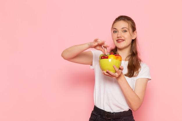Vista frontal de uma jovem mulher de camiseta branca segurando um prato com frutas frescas