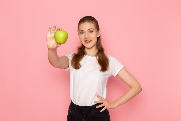 Vista frontal de uma jovem mulher de camiseta branca segurando uma maçã verde com um sorriso na parede rosa claro