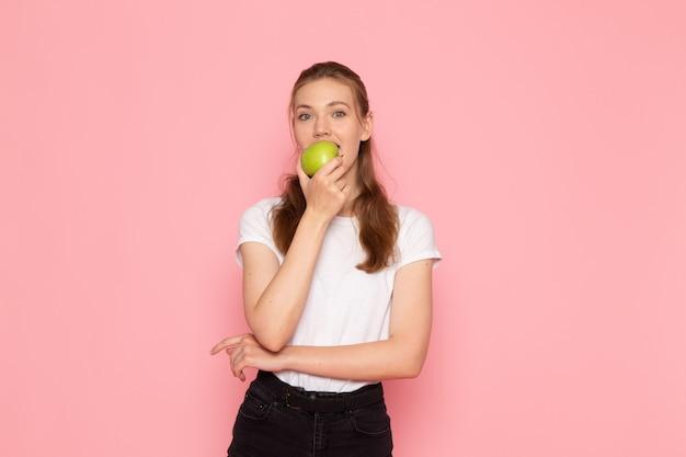 Vista frontal de uma jovem mulher de camiseta branca segurando uma maçã verde e mordendo-a na parede rosa