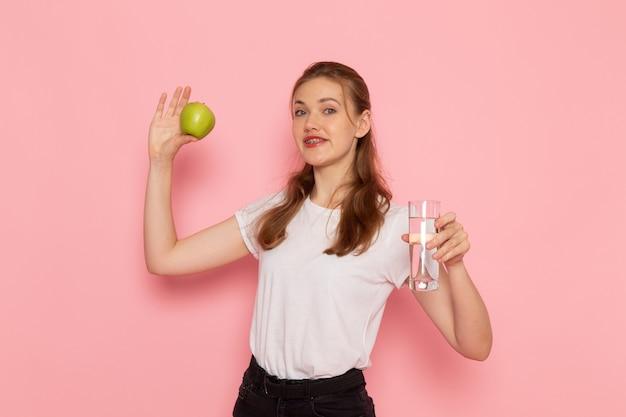 Vista frontal de uma jovem mulher de camiseta branca segurando uma maçã verde e um copo d'água na parede rosa