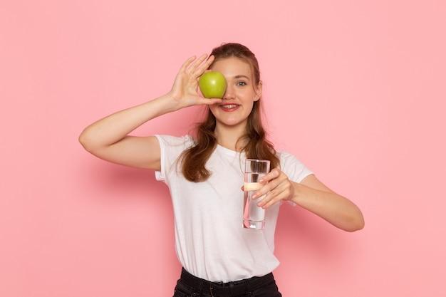 Vista frontal de uma jovem mulher de camiseta branca segurando uma maçã verde e um copo d'água sorrindo na parede rosa
