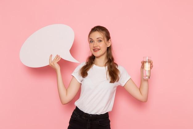 Vista frontal de uma jovem mulher de camiseta branca segurando uma placa branca e um copo de água na parede rosa