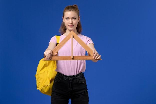 Vista frontal de uma jovem mulher de camiseta rosa segurando a figura do triângulo de madeira na parede azul
