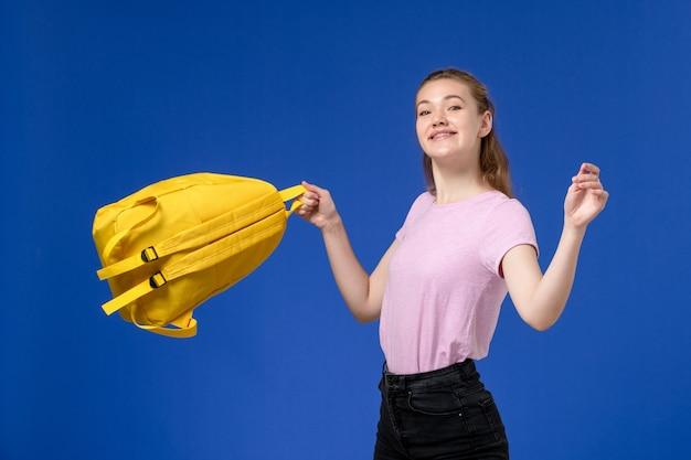 Vista frontal de uma jovem mulher de camiseta rosa segurando uma mochila amarela, sorrindo na parede azul