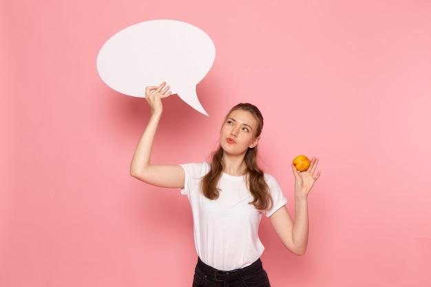 Vista frontal de uma jovem mulher em uma camiseta branca segurando pêssego fresco e uma placa branca na parede rosa claro