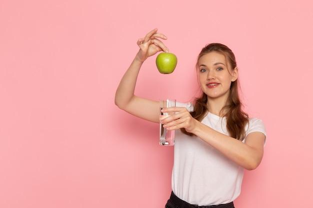 Vista frontal de uma jovem mulher em uma camiseta branca segurando uma maçã verde fresca e um copo d'água