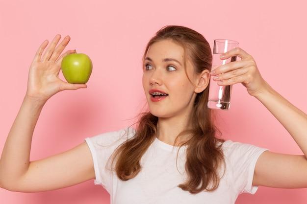 Vista frontal de uma jovem mulher em uma camiseta branca segurando uma maçã verde fresca e um copo de água na parede rosa