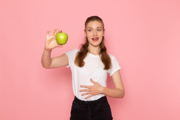 Vista frontal de uma jovem mulher em uma camiseta branca segurando uma maçã verde fresca na parede rosa claro