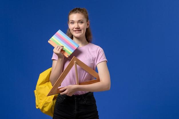 Vista frontal de uma jovem mulher em uma camiseta rosa segurando uma figura triangular de madeira e um caderno sorrindo na parede azul