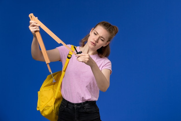 Vista frontal de uma jovem mulher em uma camiseta rosa, usando uma mochila amarela, segurando uma figura de madeira na parede azul
