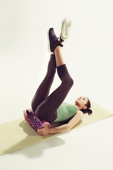 Vista frontal de uma jovem mulher, esticando o corpo na aula de ginástica.