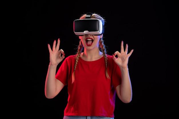 Vista frontal de uma jovem mulher jogando realidade virtual em uma fantasia de ultrassom de jogo escuro