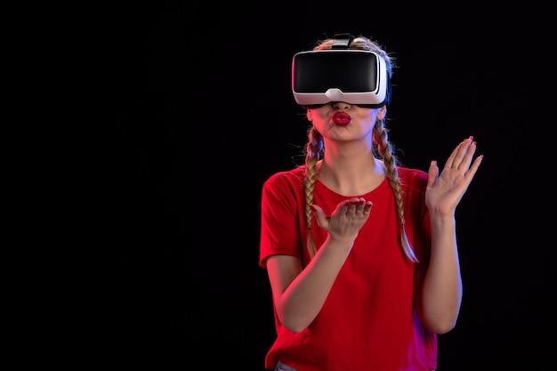 Vista frontal de uma jovem mulher jogando realidade virtual na parede escura