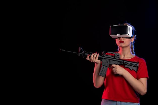 Vista frontal de uma jovem mulher jogando vr com uma parede escura de rifle de brinquedo