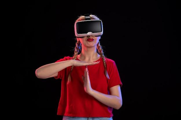 Vista frontal de uma jovem mulher jogando vr na parede escura