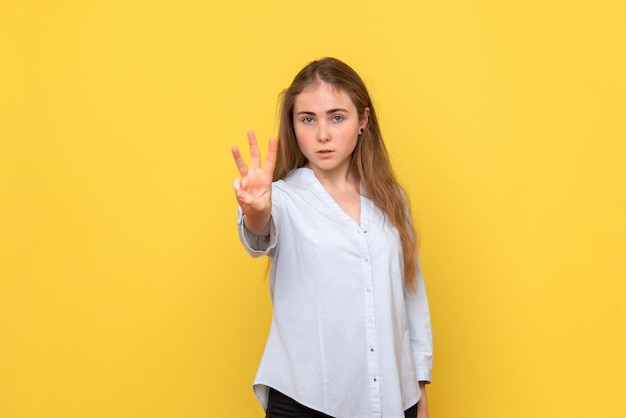 Vista frontal de uma jovem mulher mostrando o número