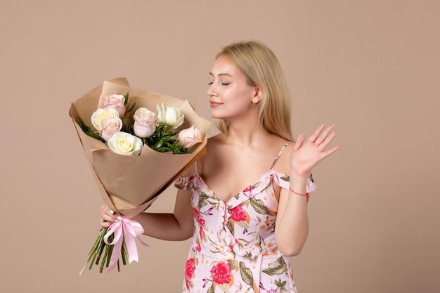 Vista frontal de uma jovem mulher posando com um buquê de lindas rosas na parede marrom