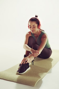 Vista frontal de uma jovem mulher sentada com fones de ouvido na aula de ginástica.