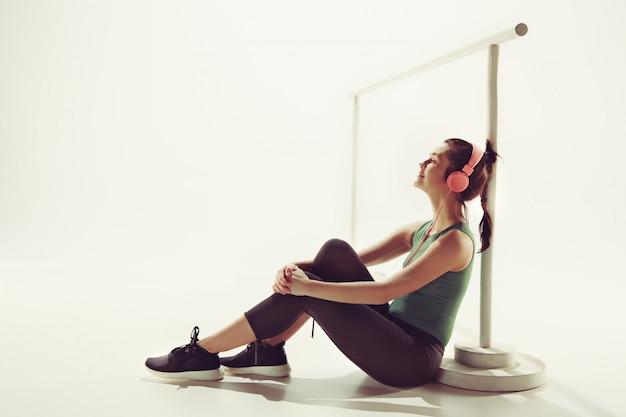 Vista frontal de uma jovem mulher sentada com fones de ouvido