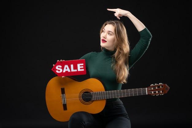 Vista frontal de uma jovem musicista segurando um violão e mostrando a venda apontando algo no lado direito no escuro