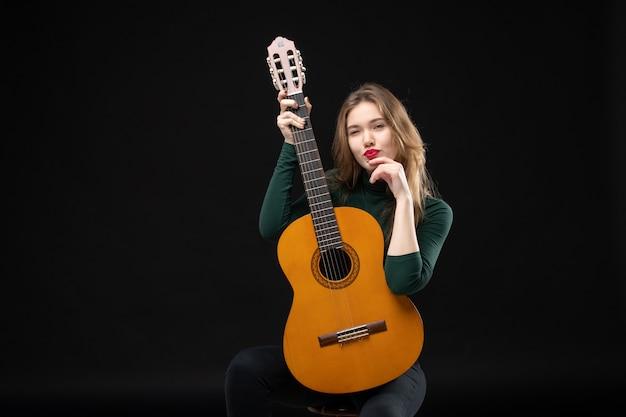 Vista frontal de uma jovem musicista segurando uma guitarra e olhando algo com cuidado no escuro