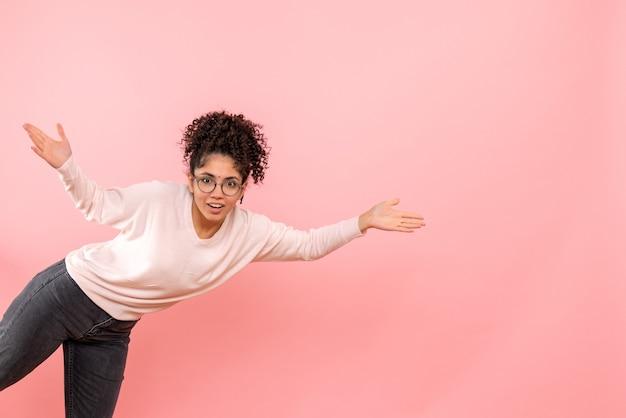 Vista frontal de uma jovem na parede rosa