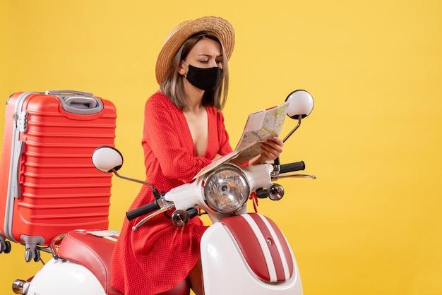 Vista frontal de uma jovem ocupada com máscara preta, olhando para o mapa perto da motocicleta