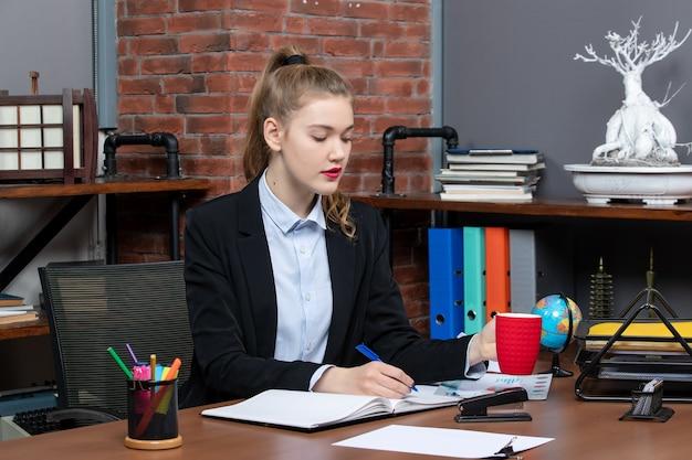 Vista frontal de uma jovem ocupada sentada à mesa segurando um copo vermelho, escrevendo em um documento no escritório