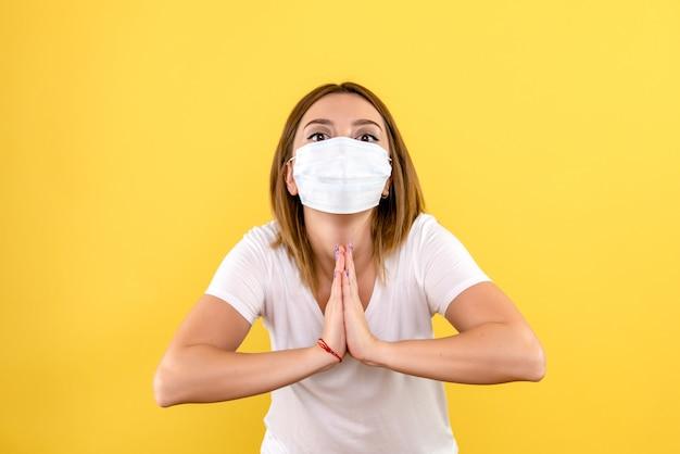 Vista frontal de uma jovem orando com uma máscara na parede amarela