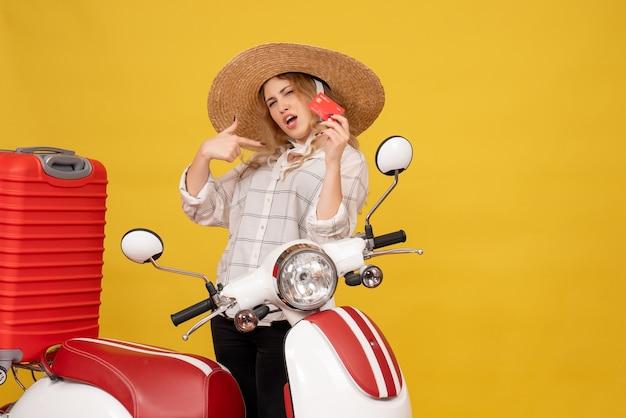 Vista frontal de uma jovem orgulhosa e ambiciosa de chapéu, recolhendo a bagagem, sentada em uma motocicleta e segurando o cartão do banco