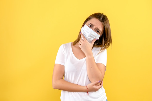 Vista frontal de uma jovem pensando em máscara na parede amarela