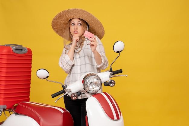 Vista frontal de uma jovem pensativa com chapéu, recolhendo a bagagem, sentada na motocicleta e segurando o cartão do banco