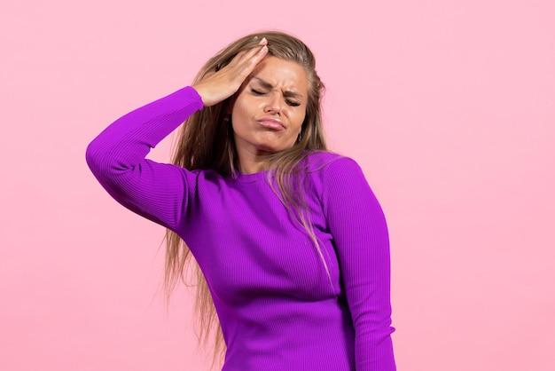 Vista frontal de uma jovem posando com um lindo vestido roxo na parede rosa