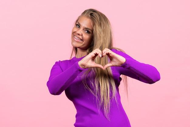 Vista frontal de uma jovem posando com um sorriso em um lindo vestido roxo na parede rosa