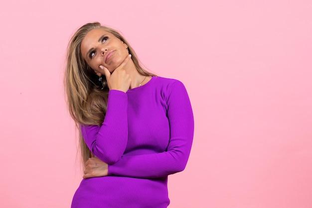 Vista frontal de uma jovem posando e pensando em um lindo vestido roxo na parede rosa